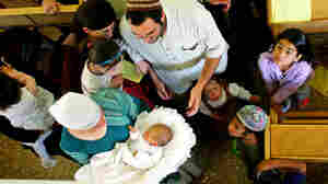 Family members and friends gather around 8-day-old Israeli baby Oz Naftaly Cohen after his traditional Jewish circumcision ceremony in 2005.