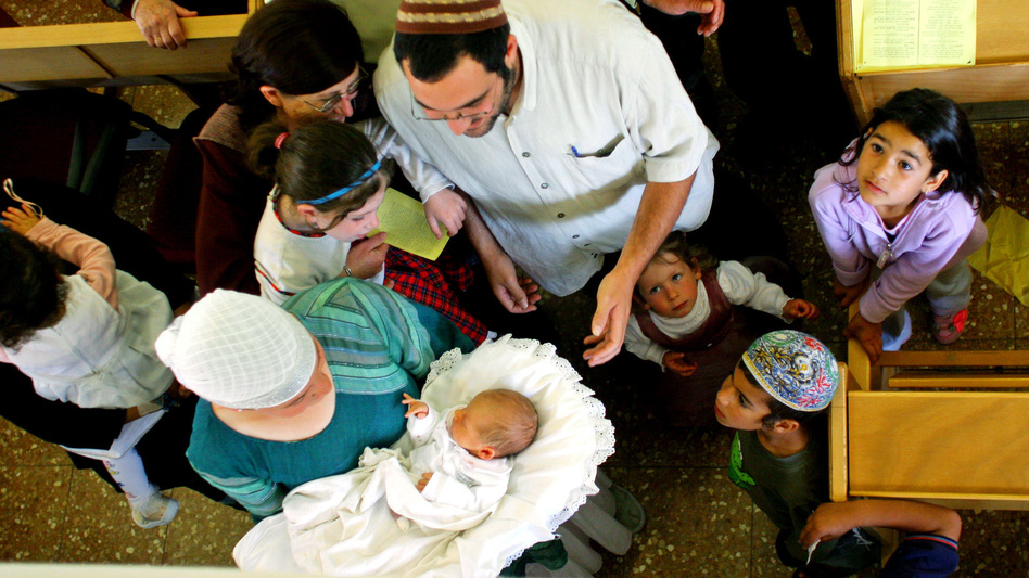 Family members and friends gather around 8-day-old Israeli baby Oz Naftaly Cohen after his traditional Jewish circumcision ceremony in 2005. (AP)