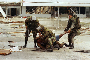 Members of the Florida National Guard subdue a man outside the Cutler Ridge shoe store. The unidentified man, carrying a firearm, was wrestled to the ground after guard members thought he was looting the store.