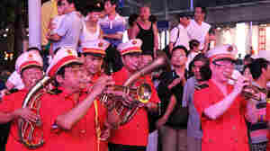 "The ""Loving Happiness Band,"" supported, in part, by the Communist Party, plays for a crowd on Nanjing Road."