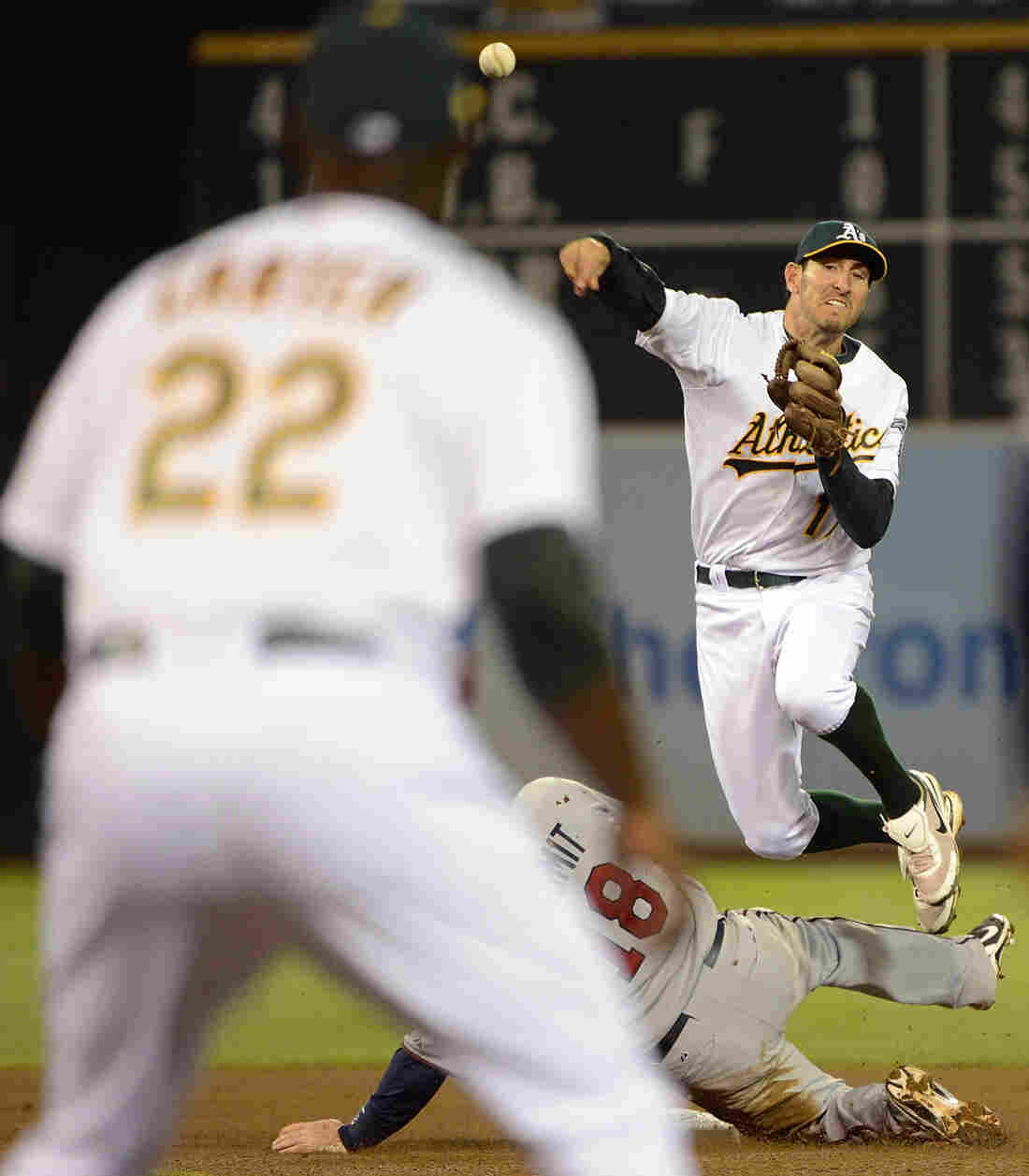 Adam Rosales of the Oakland Athletics gets his throw off to Chris Carter at first base to complete Tuesday night's triple play.