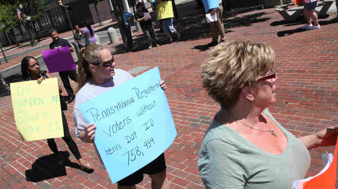 Protesters hold signs in Allentown, Pa., om July 25 as the Commonwealth Court holds hearings on voter ID laws.
