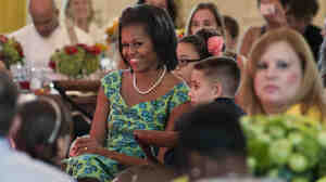 First lady Michelle Obama sits with guests as they eat lunch during a kids' state dinner at the White House on Monday.