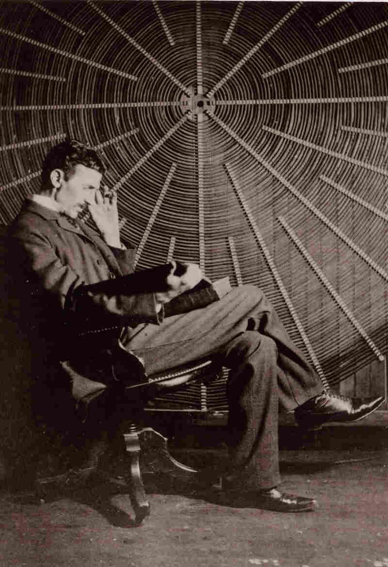 Tesla reads in front of the spiral coil of his high-frequency transformer at his lab on Houston Street in New York.