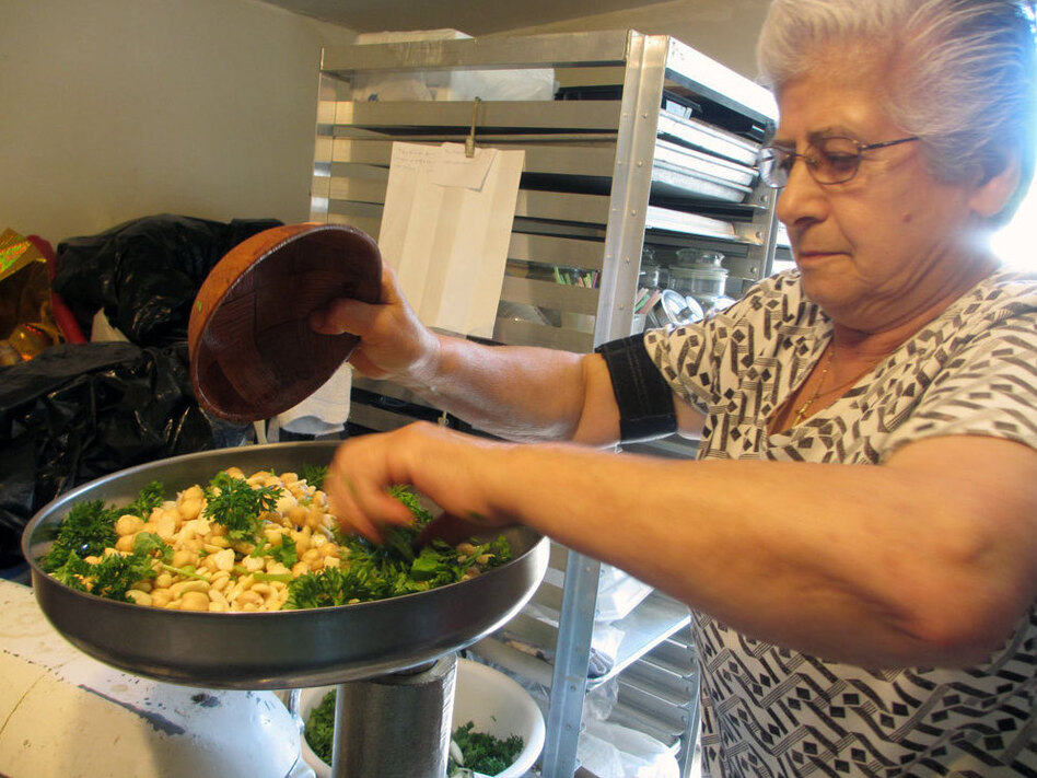 Leila Sfeir mixes her Lebanese-style falafel, which includes lots of green herbs. (NPR)