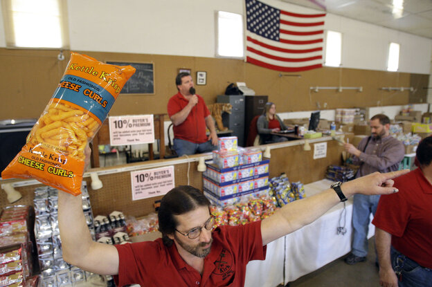 Runner Tom Howard holds up the merchandise at a grocery auction in Dallas, Pa., in 2009. These auctions are becoming more popular as people look for deals on food that's past its prime.
