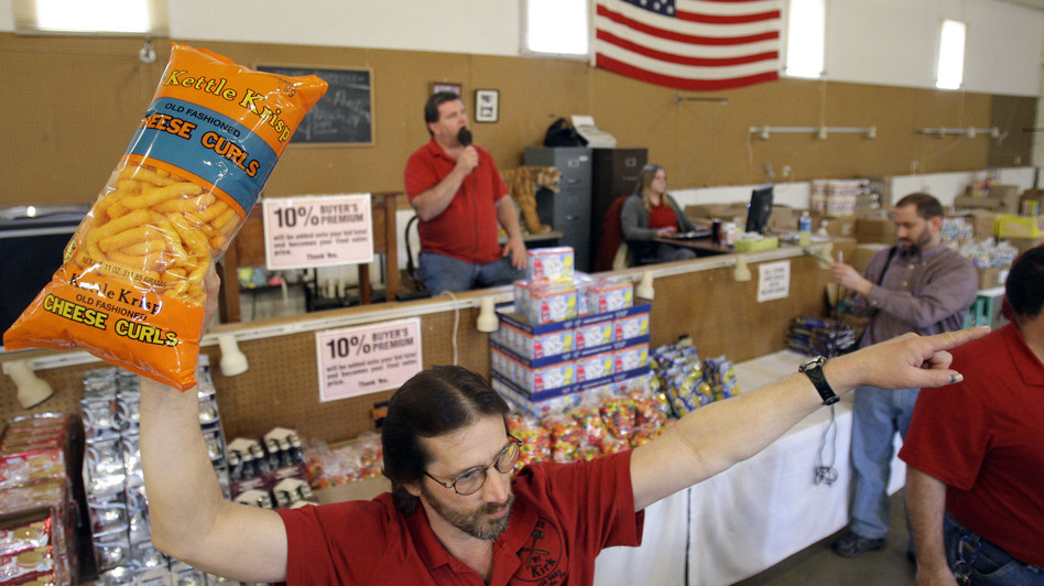 Runner Tom Howard holds up the merchandise at a grocery auction in Dallas, Pa., in 2009. These auctions are becoming more popular as people look for deals on food that's past its prime. (AP)