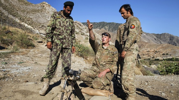 """Spc. Ben Purvis (center) helps train Afghan troops on how to use mortars in the eastern province of Kunar in June. The top U.S. commander in Afghanistan, Gen. John Allen, points to several factors in the rise of """"insider attacks"""" on American forces. He says relations between U.S. and Afghan troops are good overall. (Reuters/Landov)"""