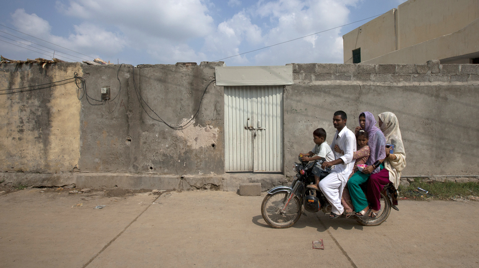 A family rides past the house of Rimsha Masih, a Pakistani Christian girl arrested on blasphemy charges, on the outskirts of Islamabad, Pakistan, on Thursday. Rimsha is accused of burning pages of Quranic verse — a crime punishable by death in Pakistan. Her case has reignited debate over the country's blasphemy law and the growing influence of Muslim extremists. (Reuters/Landov)