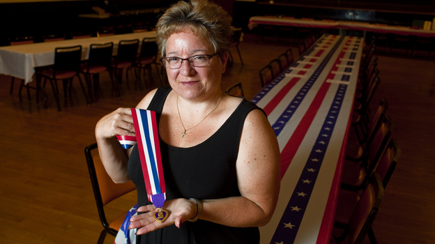 Retired Army Major Michelle Dyarman holds the Purple Heart medal she was awarded after suffering a severe concussion from an IED in Baghdad in 2005. (Robb Hill for NPR)