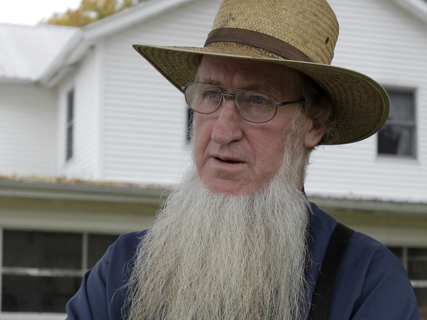 Sam Mullet, in the front yard of his home in Bergholz, Ohio, last year, is one of 16 people charged in beard- and hair- cutting attacks on fellow Amish. Mullet denies being involved in the attacks. (AP)