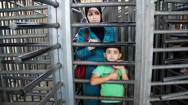 A mother and son wait to enter Israel through the Qalandia checkpoint, which separates the West Bank and Jerusalem. Most of the year, Israel permits relatively few Palestinians to visit, but over the Muslim holy month of Ramadan, 1.2 million Palestinians were allowed in.