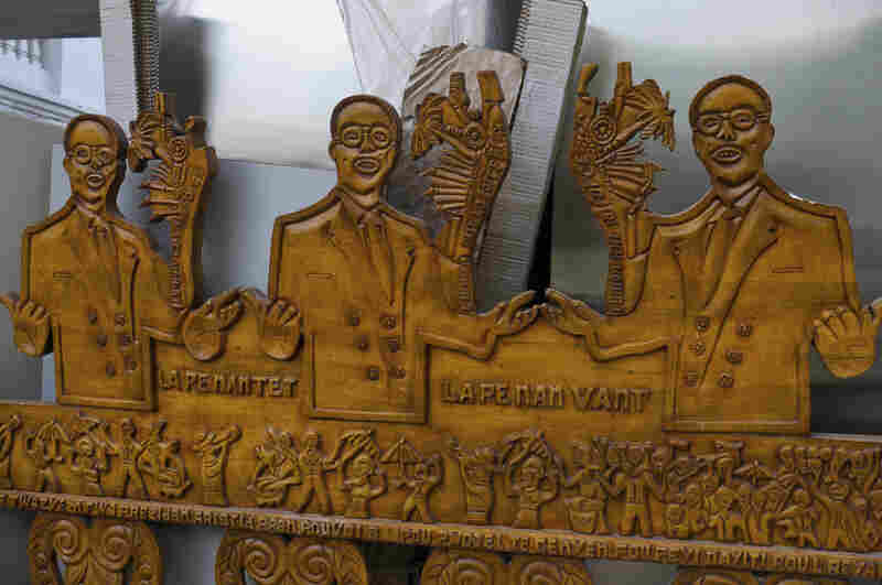 "A wooden sculpture depicting former Haitian President Jean-Bertrand Aristide rests against a wall of the National Palace. The words on the sculpture that read ""Lape nan tet, lape nan vant,"" is a slogan attributed to Aristide, meaning, ""There is no peace of mind without peace in the stomach."""