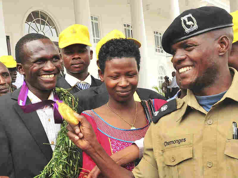 A Ugandan Army officer admires Kiprotich's gold medal at the president's residence, outside the capital Kampala, on Aug. 15. In the center is Kiprotich's wife, Patricia.