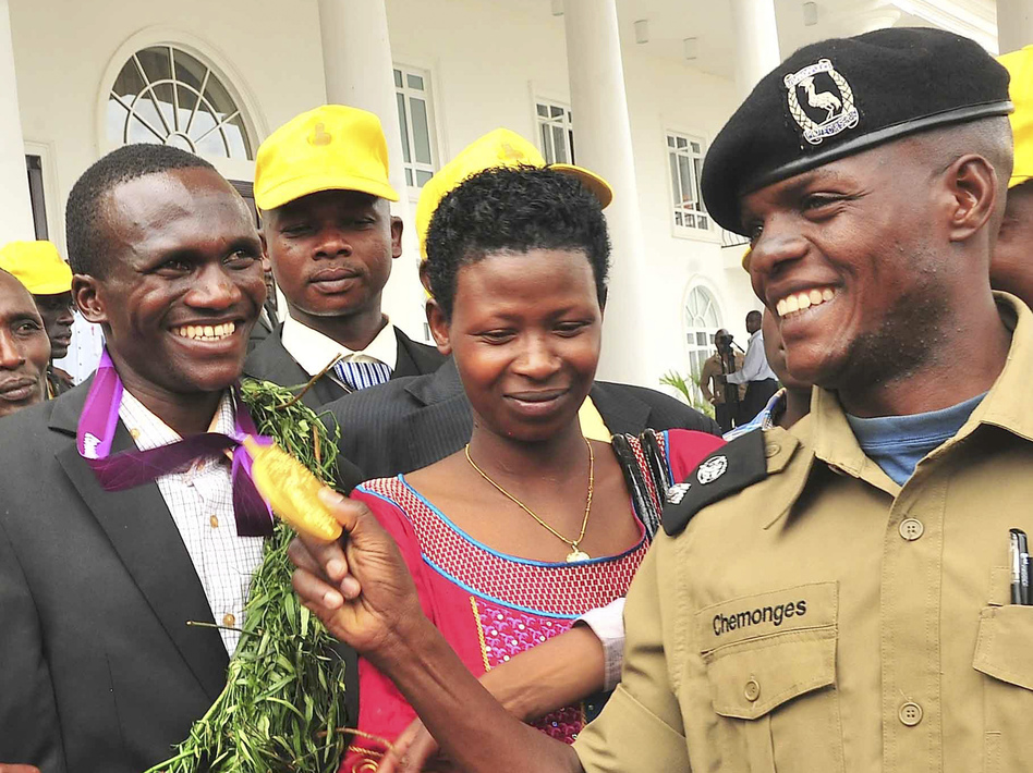 A Ugandan Army officer admires Kiprotich's gold medal at the president's residence, outside the capital Kampala, on Aug. 15. In the center is Kiprotich's wife, Patricia. (AP)