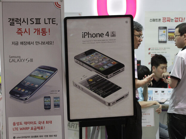 Banners advertising Samsung Electronics' Galaxy S III and Apple's iPhone 4S are displayed at a store in Seoul, South Korea.