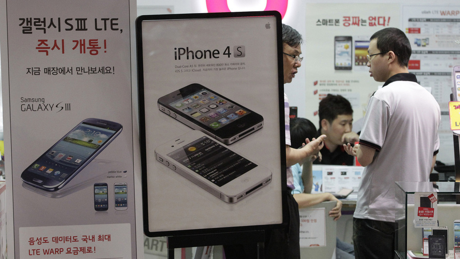 Banners advertising Samsung Electronics' Galaxy S III and Apple's iPhone 4S are displayed at a store in Seoul, South Korea. (AP)