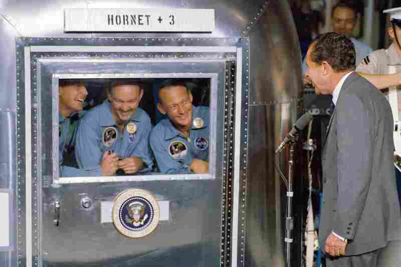 President Richard Nixon welcomes the Apollo 11 astronauts aboard the USS Hornet, prime recovery ship for the lunar landing mission. Armstrong (left) and his fellow colleagues are in the mobile quarantine facility.