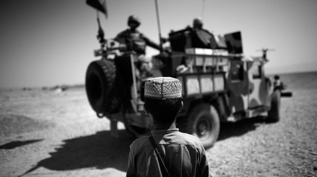A boy watches a group of Afghan and U.S. commandos in their up armored Humvee in Shindand Afghanistan. The special forces have become more prominent in the U.S. war effort. (NPR)