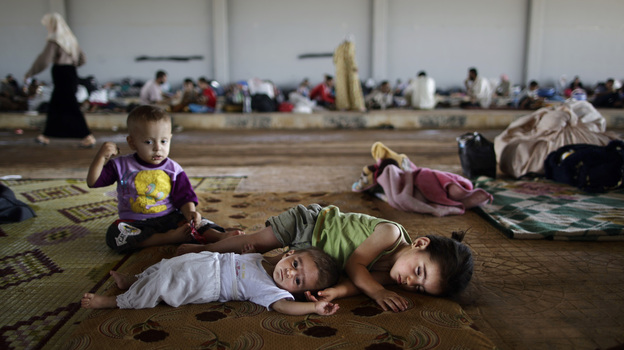 Syrian children, who fled their home with their family, take refuge at the Bab Al-Salameh border crossing, in hopes of entering one of the refugee camps in Turkey on Sunday. (AP)