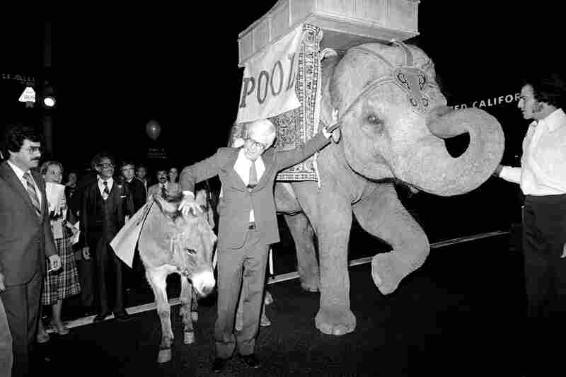 John Anderson (center), who made an independent bid for president in 1980, takes measure of a donkey and an elephant outside his campaign headquarters in Los Angeles. Campaign aides, poking fun at reporters covering Anderson, indicated that the elephant would serve as the media bus and the donkey the media car in the Los Angeles area.