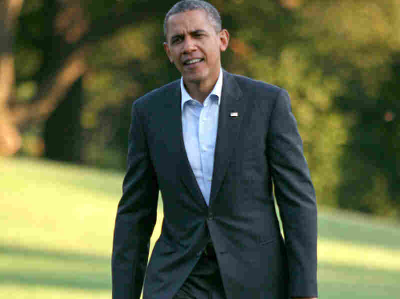 President Barack Obama walks across the South Lawn to the White House after returning from campaigning August 18, 2012 in Washington D.C.