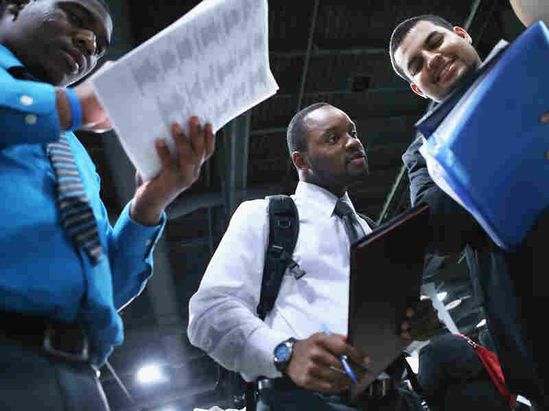 Young job-seekers look over a list of 85 business participating in a job fair last week in Washington, D.C.