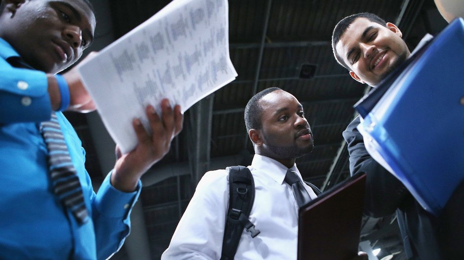 Young job-seekers look over a list of 85 business participating in a job fair last week in Washington, D.C. (Getty Images)
