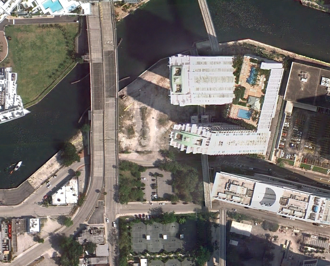 A Google Earth image from March 2011 shows the area Brickell Green Space envisions as a park. The plot is directly south of the river, to the left of the high-rises.