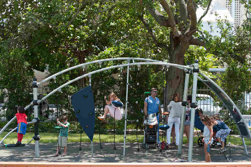 Children play at the 1814 Brickell Park, a new park that features benches, a paved path and a monument made of a girder from the World Trade Center.