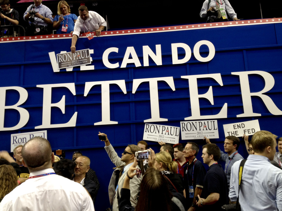 """Ron Paul supporters pose with posters on the floor of the RNC on Monday in Tampa. They put """"Ron Paul"""" over the word """"We"""" on a GOP sign that says """"We Can Do Better."""" (Liz Halloran/NPR)"""