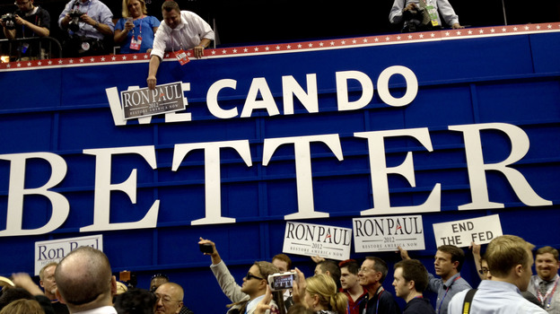 """Ron Paul supporters pose with posters on the floor of the RNC on Monday in Tampa. They put """"Ron Paul"""" over the word """"We"""" on a GOP sign that says """"We Can Do Better."""" (NPR)"""