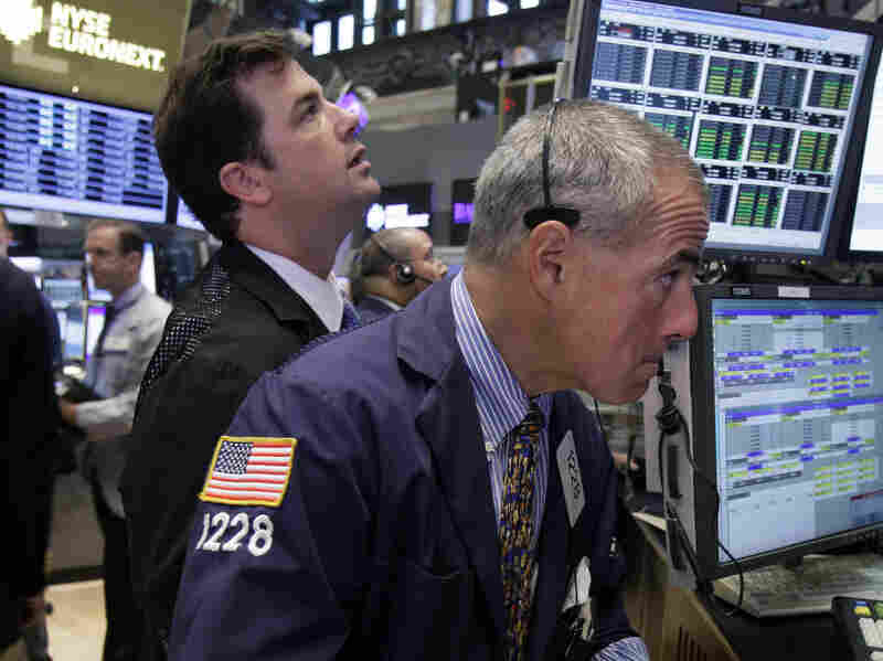 Traders work on the floor of the New York Stock Exchange. The Dow Jones industrial average is nearly back to where it was before the recession hit in 2007.