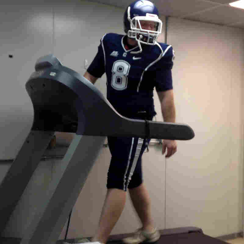 Doctoral student Brett Comstock wears a football uniform as he walks on a treadmill at the Korey Stringer Institute at the University of Connecticut.