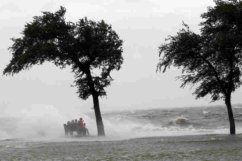 People sit on a bench near Lake Pontchartrain in New Orleans on Tuesday. Hurricane Isaac slammed into the southern Louisiana coast late Tuesday, sending floodwaters surging and unleashing fierce winds,