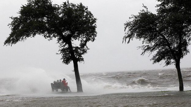 People sit on a bench along the seawall in the storm surge from Isaac, on Lakeshore Drive along Lake Pontchartrain, as the storm approaches landfall, in New Orleans, Tuesday, Aug. 28. (AP)