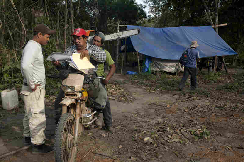 """Loggers discuss the day's plan in a camp called Puesto Viejo, or """"old post."""""""