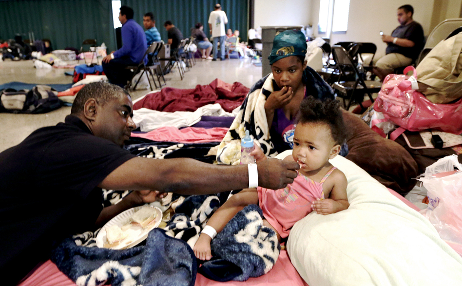 Gus Williams feeds his step-granddaughter, Somaya Washington, as her mother, Areonisha Washington, watches. They evacuated to a shelter in Houma, La. (AP)