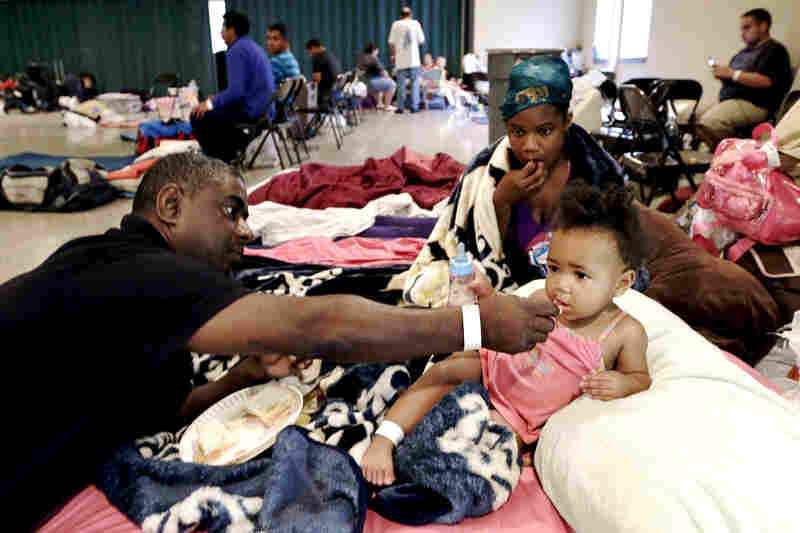 Gus Williams feeds his step-granddaughter, Somaya Washington, as her mother, Areonisha Washington, watches. They evacuated to a shelter in Houma, La.