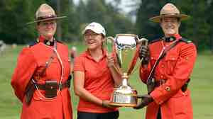 Lydia Ko accepts her winner's trophy at the CN Canadian Women's Open in Vancouver, surrounded by members of the RCMP.