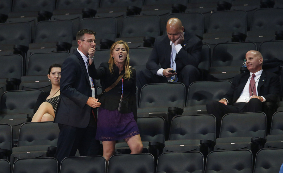 """A demonstrator shouting """"Stop the War on Women"""" screams during Rick Santorum's speech before being escorted out of the arena by security. (Reuters/Landov)"""