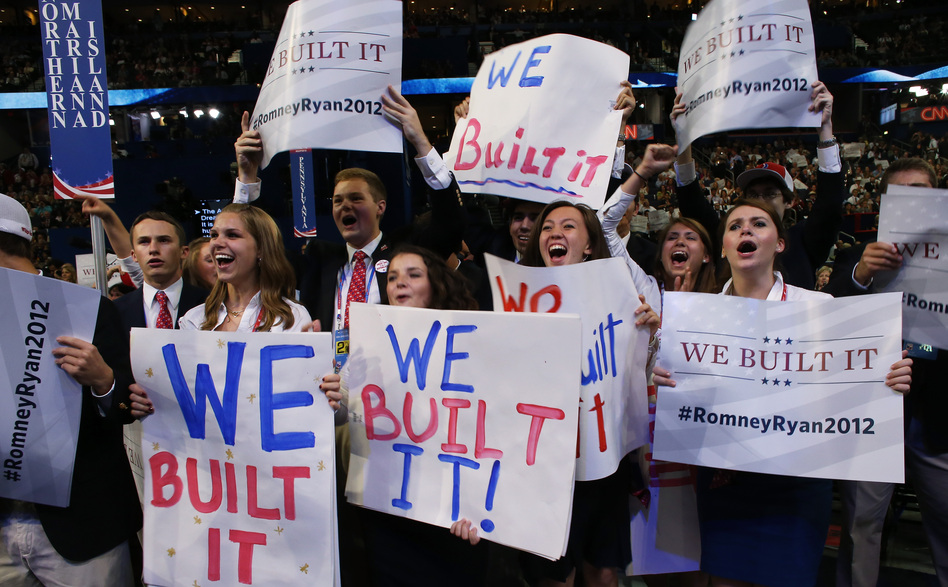 """People hold signs that read """"We Built It"""" during the convention. (Getty Images)"""