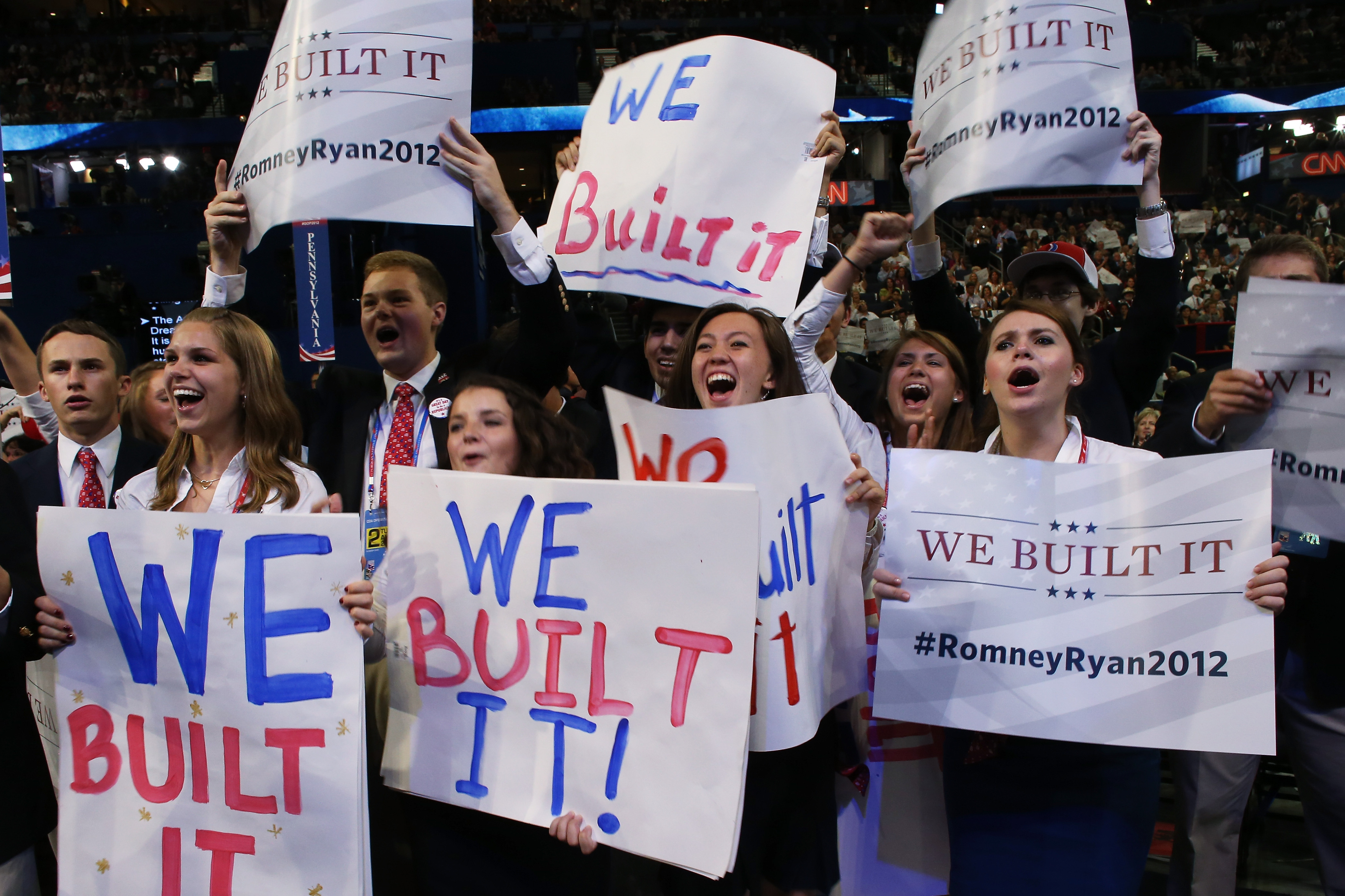 "People hold signs that read ""We Built It"" during the convention."