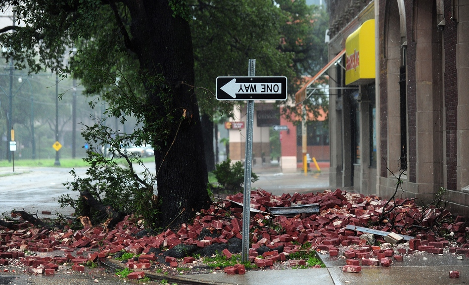A street sign is turned upside down and bricks cover the sidewalk of a deserted street in New Orleans. (AFP/Getty Images)