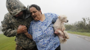 First responders carry people across the top of the levee from Plaquemines Parish to St. Bernard Parish as Hurricane Isaac sends powerful winds and rain through the area.