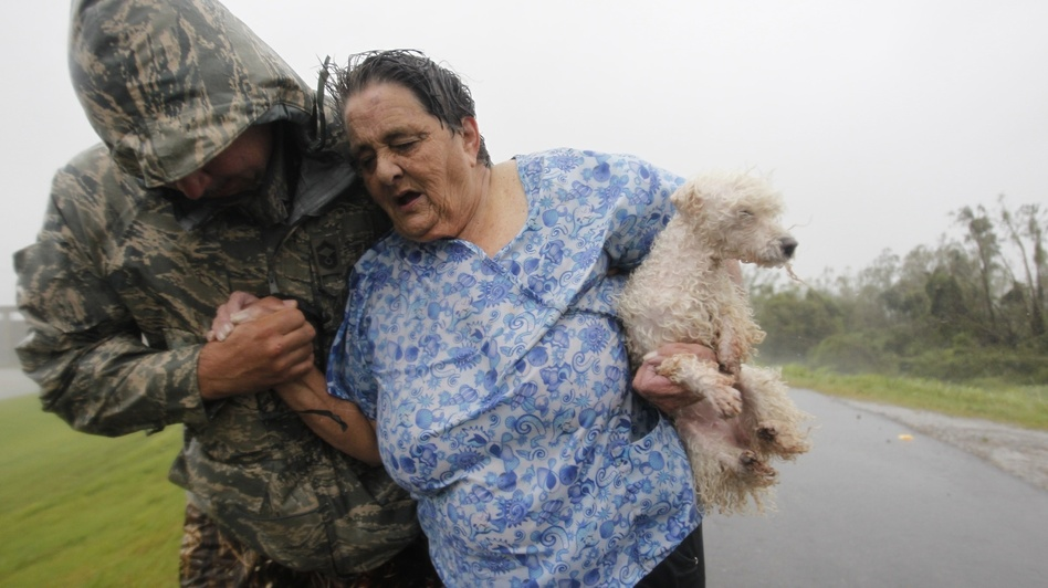 First responders carry people across the top of the levee from Plaquemines Parish to St. Bernard Parish as Hurricane Isaac sends powerful winds and rain through the area. (The Times-Picayune/Landov)