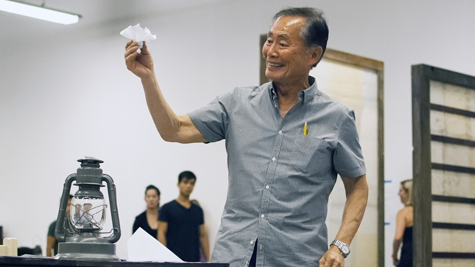 Takei rehearses a scene in which his character, Ojii-San, tries to cheer his granddaughter up by making her an origami flower out of a loyalty questionnaire. (Courtesy of The Old Globe)