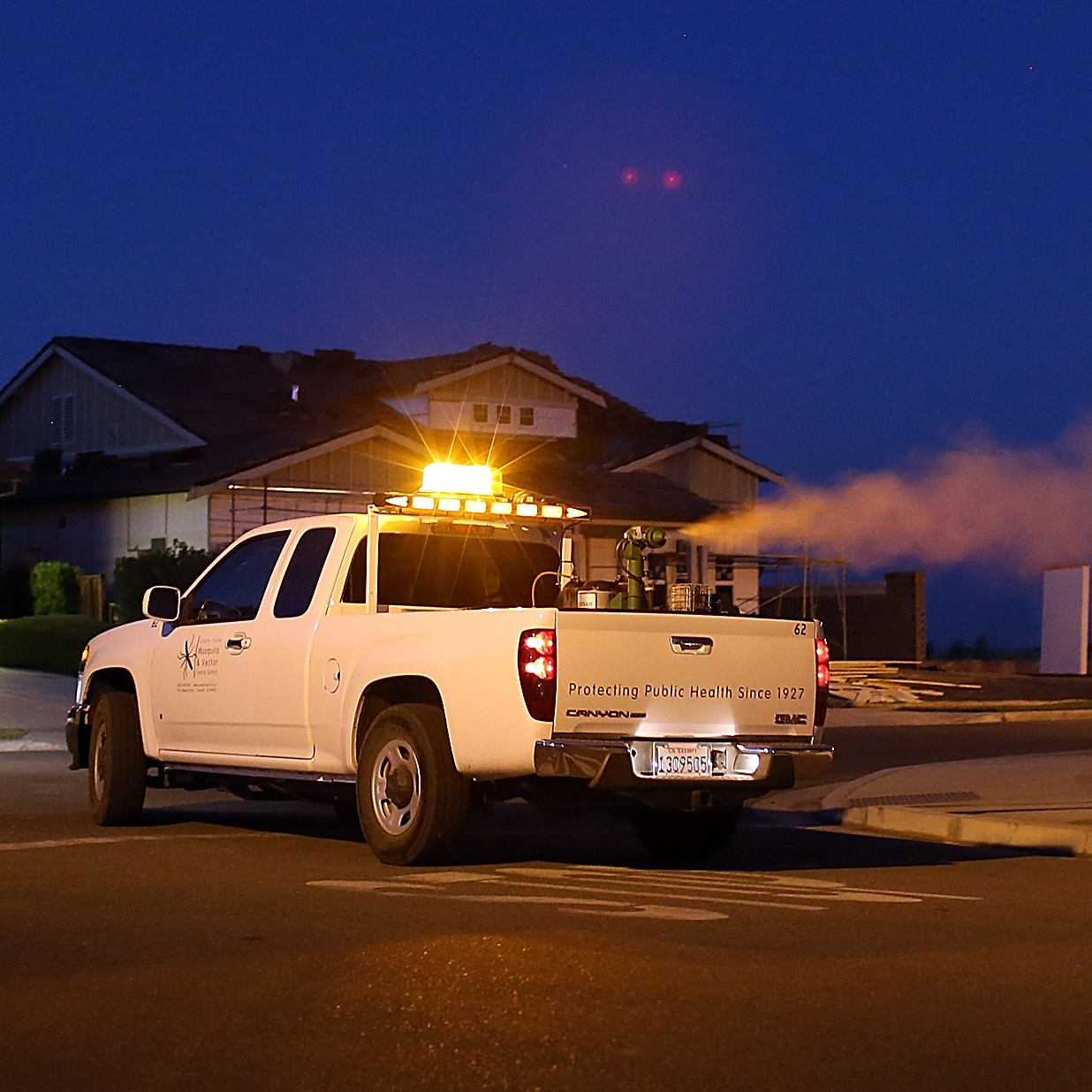 Technicians with the Contra Costa County Mosquito and Vector Control District drive a truck through a Brentwood, Calif., neighborhood fogging insecticide to curb mosquitoes that spread West Nile virus.