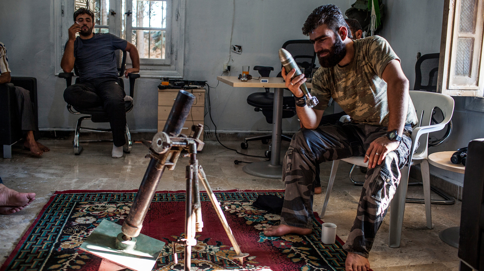 The Syrian rebels have no one source for their weapons and have had to scrape together their arsenal in various ways. Here, Abdel Hakim Yassin, a rebel commander in northern Syria, inspects a Yugoslav illumination mortar round that was brought to him by an Iraqi arms dealer. (Bryan Denton for The New York Times)