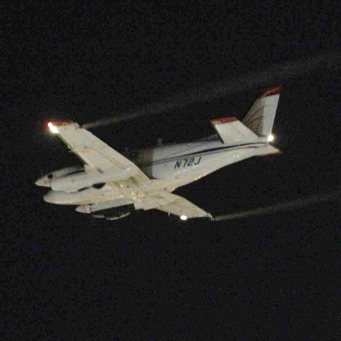 A Beechcraft airplane sprays insecticide over Dallas early Monday morning to curb the spread of West Nile virus.